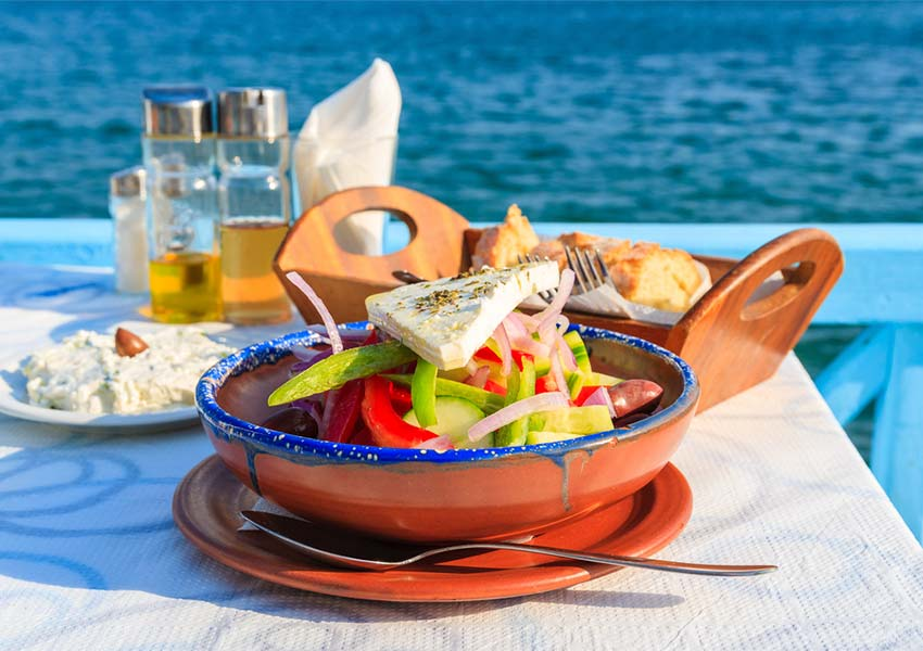 Fresh Greek Salad with Bread and Olive Oil Tasting On Samos With Aegean Sea In Background