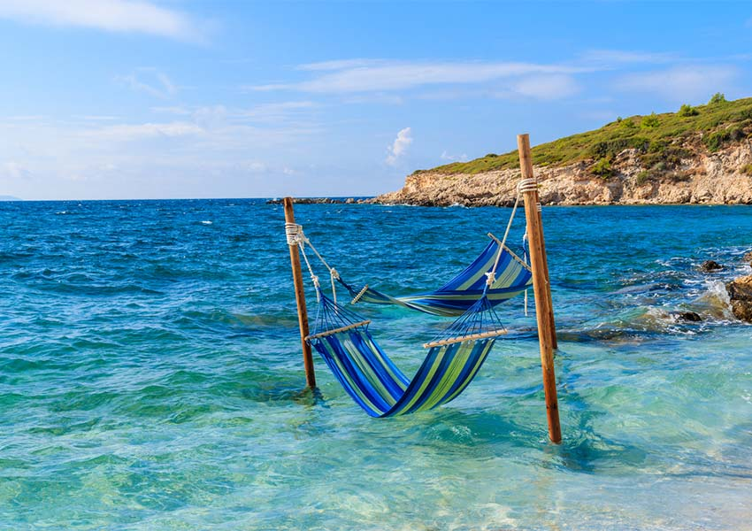 Two Hammocks To Relax Over Bright Blue Seawater In Proteas Bay On Samos